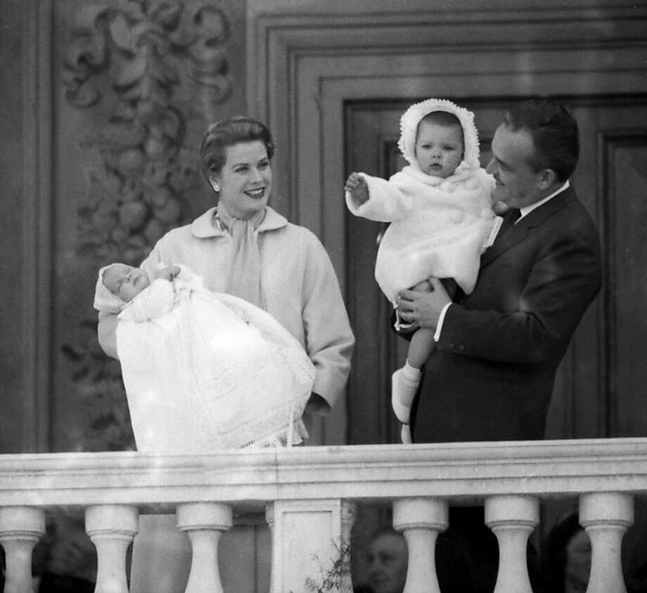 Prince Rainier of Monaco holding his daughter Caroline and Princess Grace present their newborn son Albert (in her arms) to residents of the principality, April 19, 1958 from the balcony of the palace, a day before the baptism of the child.  Photo: Stf