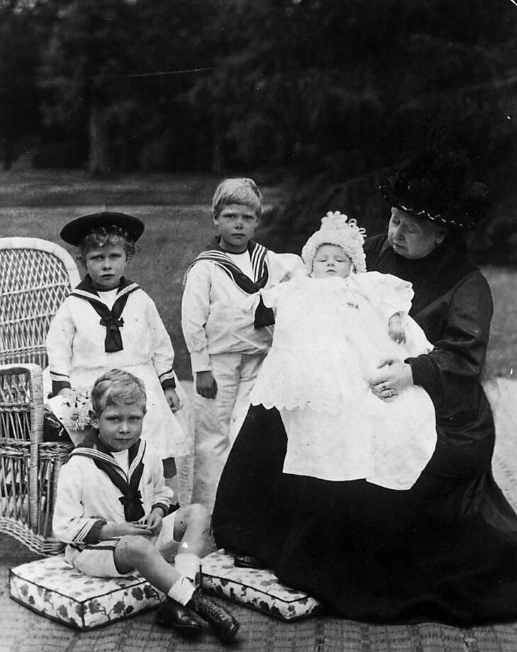Queen Victoria (1819 - 1901) at Osborne House on the Isle of Wight, in 1900,with her great-grandchildren, children of the Duke and Duchess of York (later King George V and Queen Mary of Teck). They are Princess Mary (on chair), later Countess Harewood, Prince Edward (standing), later King Edward VIII (1894 - 1972), Prince Albert (on cushion), later King George VI (1895 - 1952), and Prince Henry, Duke of Gloucester, as a baby. Photo: Hughes & Mullins