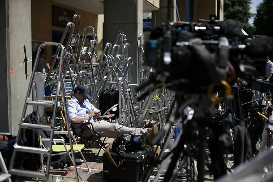 A member of a broadcast crew sits surrounded by photographers' stepladders as he waits across the street from the main entrance of St. Mary's Hospital Lindo Wing in London, Tuesday, July 9, 2013.  Media outlets are marking positions outside the building where Britain's Prince William and his wife Kate are expecting their first child to be born in mid-July.  (AP Photo/Matt Dunham) Photo: Matt Dunham, Associated Press