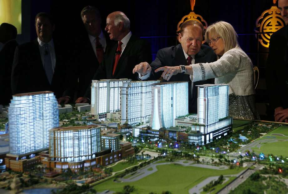 Las Vegas hotel and casino magnate Sheldon Adelson and his wife, Miriam Ochsorn, point out features of a model of a resort they were building in China's Macau region in 2012. Photo: Kin Cheung, Associated Press