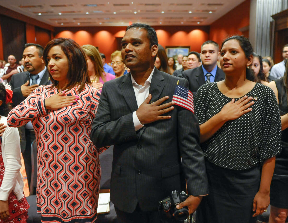 Carolina Chavez-Reyes (left) and Ravinden Andrew and wife Aruna say the Pledge of Allegiance after being naturalized during a ceremony at the Convention Center on July 4.