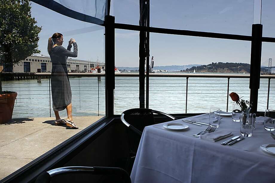 A woman outside the Waterfront Restaurant snaps photographs.. Photo: Liz Hafalia, The Chronicle
