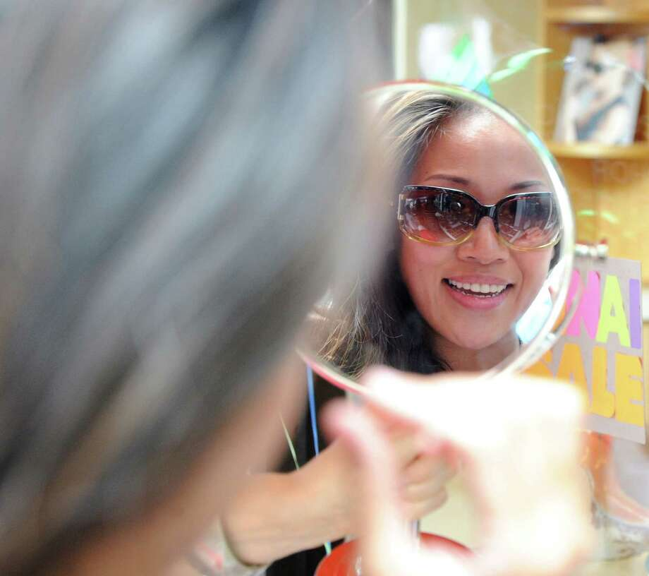 Tina Mak of Greenwich tries on Jimmy Choo sunglasses at Trapp Optical during the annual Greenwich Sidewalk Sales in the central business district of Greenwich, Thursday, July 11, 2013.  Photo: Bob Luckey / Greenwich Time