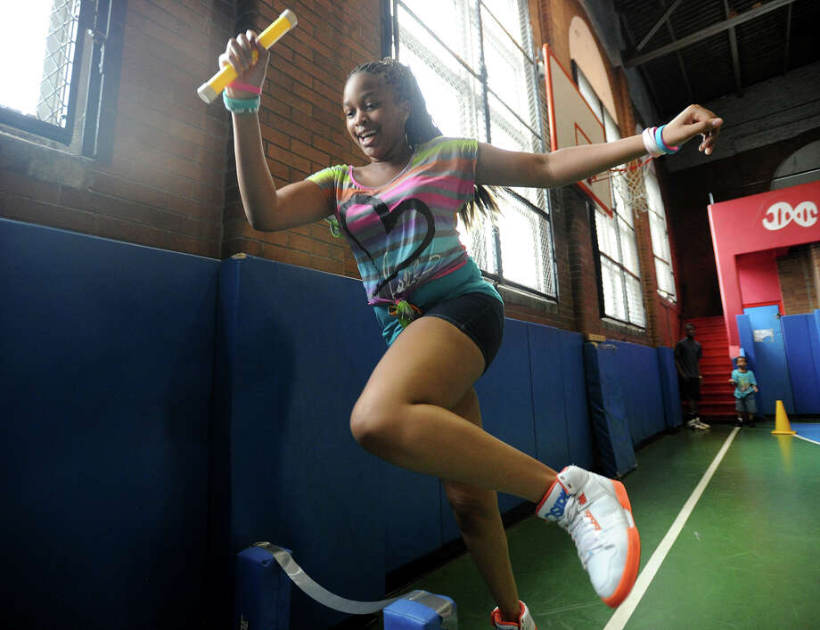 Tarah Bernard, 13, leaps over a makeshift hurdle during a relay race in the gym of the Orcutt Boys & Girls Club at 102 Park Street in Bridgeport, Conn. on Thursday, July 11, 2013. The club, which lacks air conditioning, was constructed in 1930. Photo: Brian A. Pounds / Connecticut Post