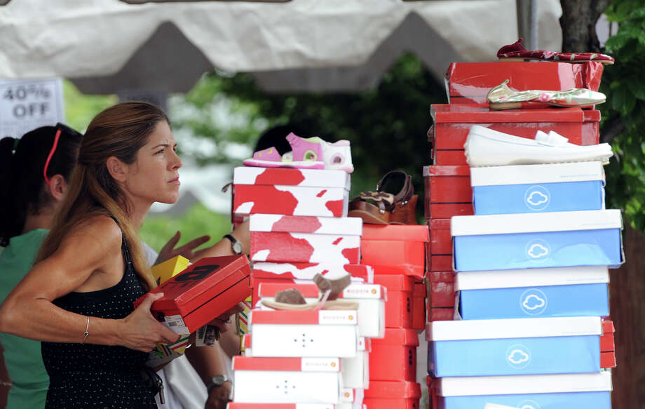 Courtenay Carella of Greenwich shops for shoes at Little Eric of Greenwich during the annual Greenwich Sidewalk Sales in the central business district of Greenwich, Thursday, July 11, 2013.  Photo: Bob Luckey / Greenwich Time