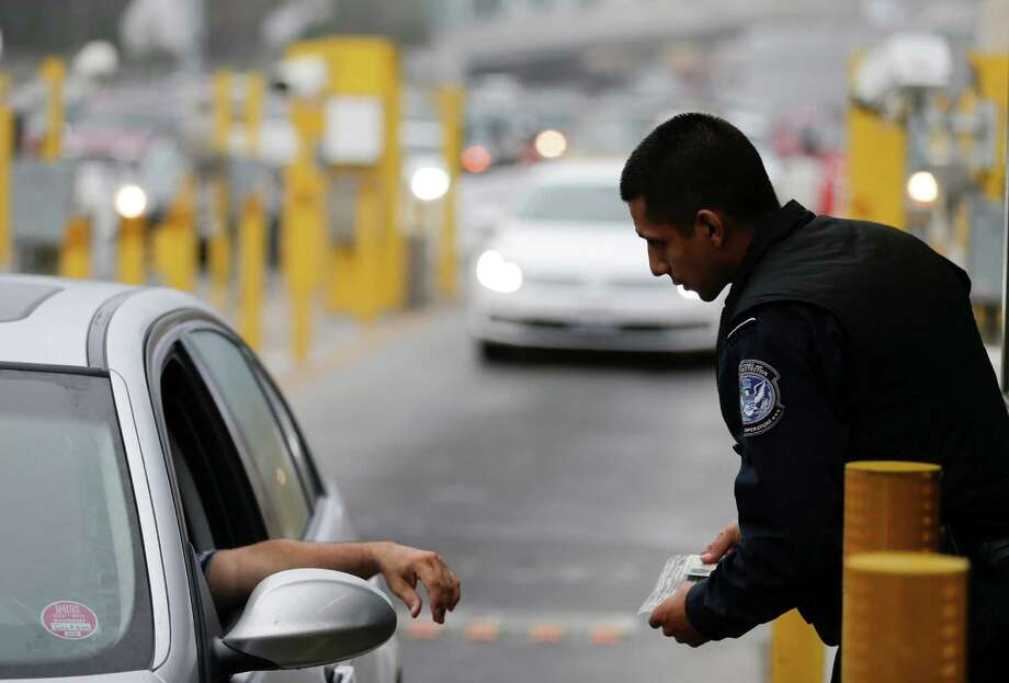 A Customs and Border Protection officer speaks to a driver  at the San Ysidro port of entry. More CBP officers  will enhance interdiction capabilities at ports and provide an economic stimulus by reducing backups. Photo: Gregory Bull, Associated Press / AP