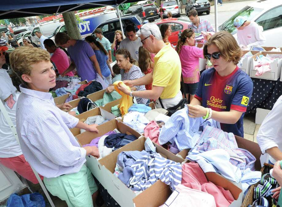 At right, Tommy Hull of Greenwich shops for clothes at Vineyard Vines during the annual Greenwich Sidewalk Sales in the central business district of Greenwich, Thursday, July 11, 2013. Shops and boutiques on Greenwich Avenue and surrounding streets are offering sales and discounted prices on a wide variety of merchandise Thursday July 11 through Sunday July 14. Photo: Bob Luckey / Greenwich Time