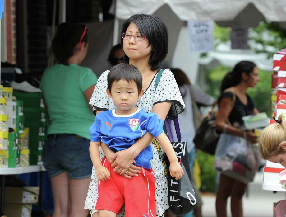 Yumi Tsuno of Greenwich carries her son, Arata, 3, through the crowd during the annual Greenwich Sidewalk Sales in the central business district of Greenwich, Thursday, July 11, 2013.  Photo: Bob Luckey / Greenwich Time