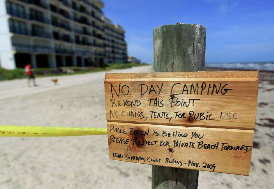 "A small hand painted sign reads ""No day camping beyond this point. No chairs, tents, for public use.  Public beach is behind you. Please respect our private beach forward"" on Hershey Beach, Thursday, July 11, 2013, in Galveston, as private beach signs go up around the area. Photo: Karen Warren, Houston Chronicle / © 2013 Houston Chronicle"