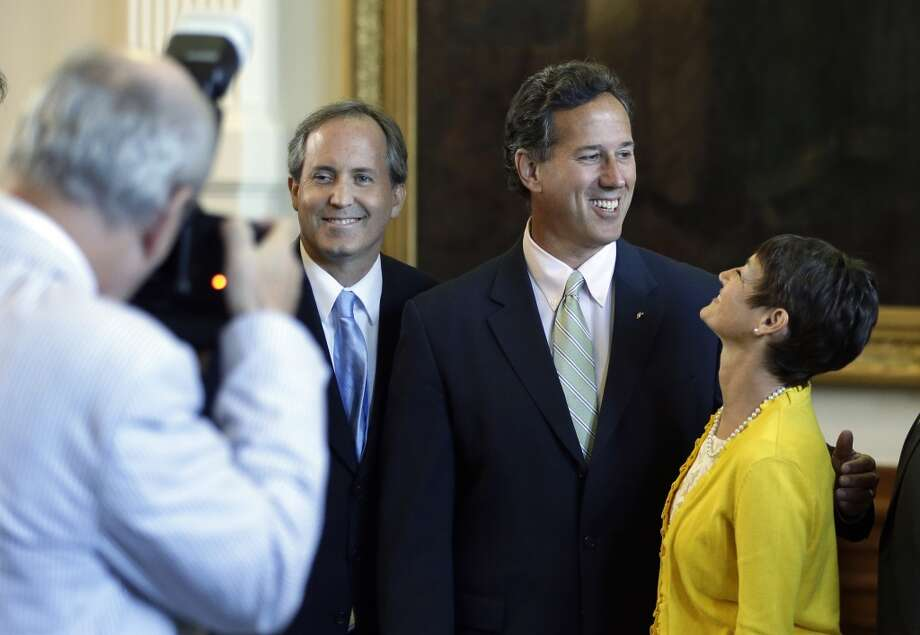 Former Pennsylvania Sen. Rick Santorum, center, poses for a photo with Sen. Donna Campbell, R- New Braunfels, right, and Sen. Ken Paxton, R-McKinney, left, in the Senate Chambers, Thursday, July 11, 2013, in Austin, Texas.  A Senate committee on Thursday pushed through new abortion restrictions, setting up a Senate vote before the weekend to send it to Gov. Rick Perry. The bill would require doctors to have admitting privileges at nearby hospitals, only allow abortions in surgical centers, dictate when abortion pills are taken and ban abortions after 20 weeks. (AP Photo/Eric Gay)