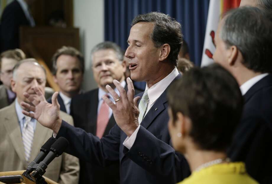 Former Pennsylvania Sen. Rick Santorum, center, speaks during a news conference outside the Senate Chambers, Thursday, July 11, 2013, in Austin, Texas.  A Senate committee on Thursday pushed through new abortion restrictions, setting up a Senate vote before the weekend to send it to Gov. Rick Perry. The bill would require doctors to have admitting privileges at nearby hospitals, only allow abortions in surgical centers, dictate when abortion pills are taken and ban abortions after 20 weeks. (AP Photo/Eric Gay)