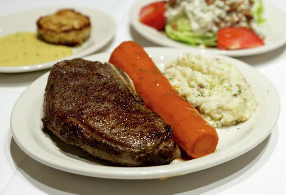 An herb rub enhances the sear on the Kansas City strip, served here with a glazed carrot and smashed potatoes. Photo: Photos By William Luther / San Antonio Express-News