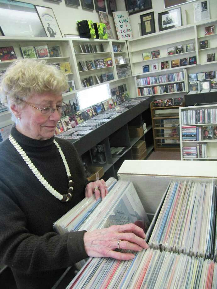 Sally White, owner of Sally's Place, flips through some music in her Main Street shop. Photo: Contributed Photo, ST / Westport News