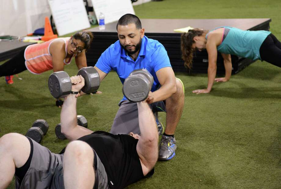 Trainer Christian Oropeza helps members with a workout at Elite Human Performance in Danbury, Conn. on Wednesday, July 10, 2013.  Club owner, Christian Oropeza recently traveled to the Phillipines to teach fitness classes. Photo: Tyler Sizemore / The News-Times