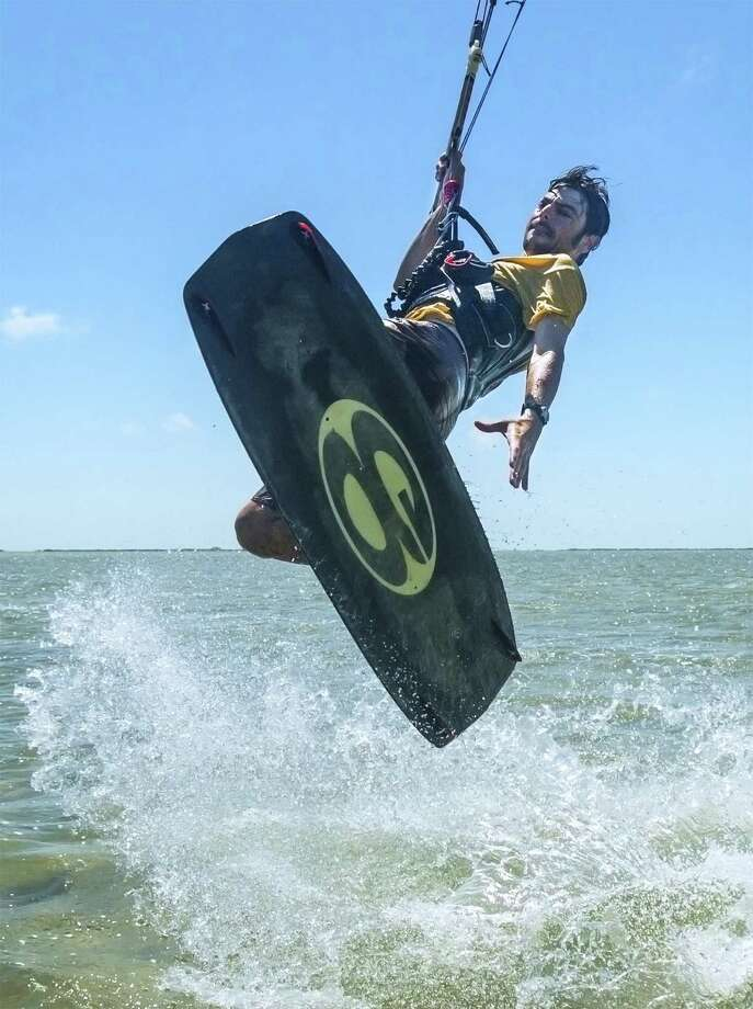"Instructor Jamie Ellwood of Third Coast Kitesurfing takes a leap while teaching a recent lesson. ""The holy grail of kitesurfing is coming back to the point you started from,"" Ellwood said. Photo: Photos By Joshua Trudell / For The Express-News"