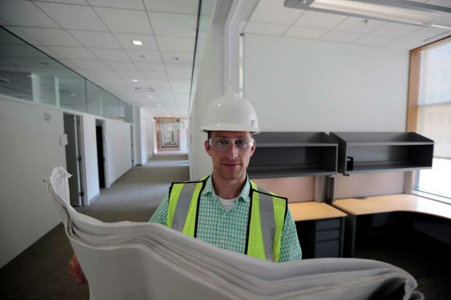 "Drew Miller, poses for a photograph, at a building under construction, Wednesday, July 10, 2013 in Silver Spring, Md. Miller quit a steady government contract job to take a chance on a company that's using ""smart technologies"" to help big corporations cut lighting costs. (AP Photo/Alex Brandon) ORG XMIT: MDAB102 Photo: Alex Brandon / AP"