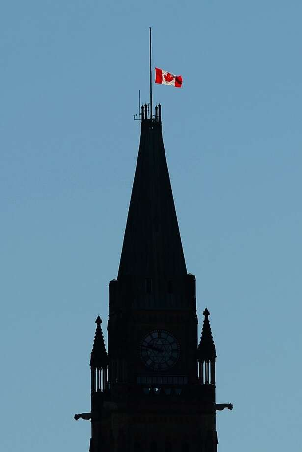 The Canadian flag of the Peace Tower flies at half-mast on Parliament Hill Ottawa on Tuesday, July 11, 2013, in Ottawa, Ontario, for victims of the  in Lac-Megantic, Quebec, train disaster. Everyone missing in the fiery crash of a runaway oil train in Quebec is presumed dead, police told grieving families, bringing the death toll to 50 in Canada's worst railway catastrophe in almost 150 years. (AP Photo/The Canadian Press, Sean Kilpatrick) Photo: Sean Kilpatrick, Associated Press