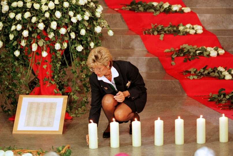 FILE - In this Sept. 11, 1998, file photo, a Swissair member lights a candle during a memorial servi