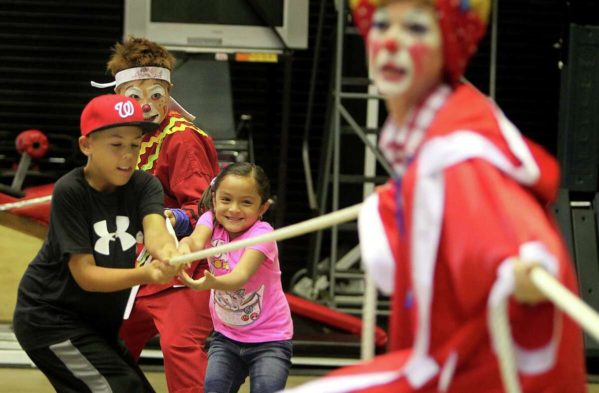Andrew Orr, 9, and Jaidan Mora, 6, play tug of war with Ringling Bros. and Barnum & Bailey clowns as they entertain HFD firefighters and their families at the Houston Fire Department's Val Jahnke Training Facility on Thursday, July 11, 2013, in Houston.
