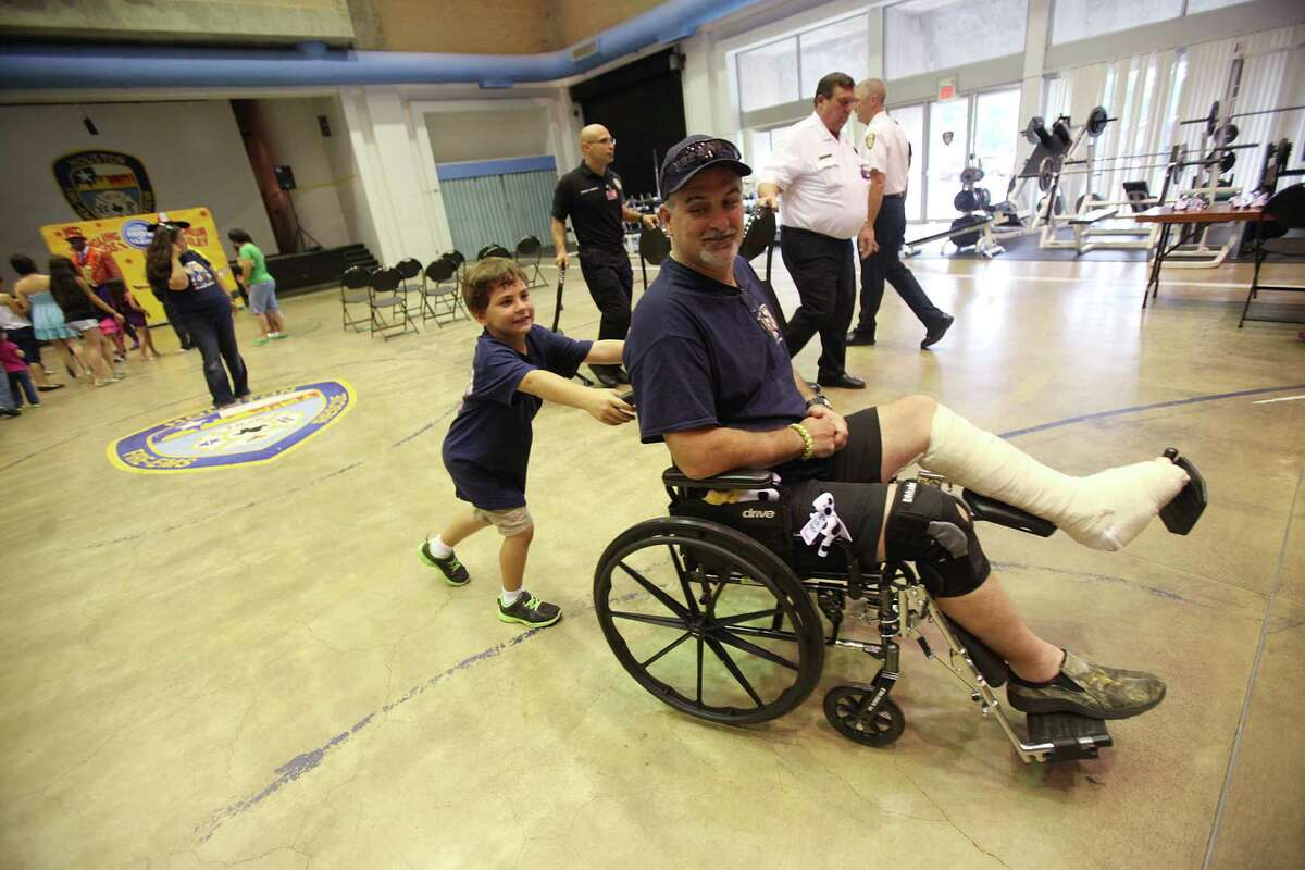 Houston Firefighter Robert Yarbrough smiles as he looks back at his step-son Austin Langley who is trying to wheel him into the lunch area after the Ringling Bros. and Barnum & Bailey performance at the Houston Fire Department's Val Jahnke Training Facility on Thursday, July 11, 2013, in Houston. Yarbrough was injured in the May hotel fire that killed four of his coworkers.