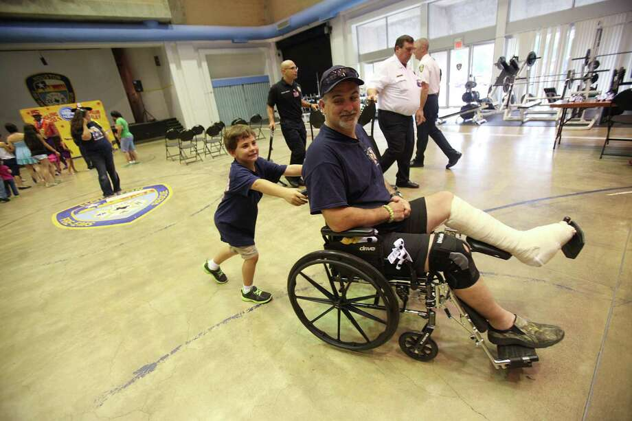 Houston Firefighter Robert Yarbrough smiles as he looks back at his step-son Austin Langley who is trying to wheel him into the lunch area after the Ringling Bros. and Barnum & Bailey performance at the Houston Fire Department's Val Jahnke Training Facility on Thursday, July 11, 2013, in Houston. Yarbrough was injured in the May hotel fire that killed four of his coworkers. Photo: Mayra Beltran / © 2013 Houston Chronicle