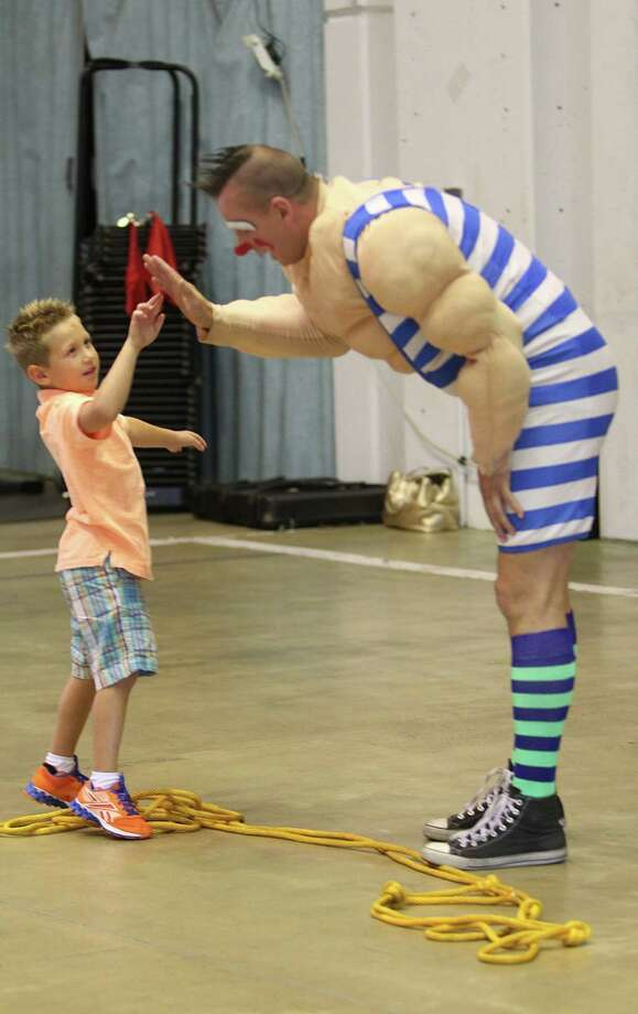 Caden Gable, 4, high-fives clown Sandor Eke after playing tug of war as Ringling Bros. and Barnum & Bailey performers entertain HFD firefighters and their families at the Houston Fire Department's Val Jahnke Training Facility on Thursday, July 11, 2013, in Houston. Photo: Mayra Beltran / © 2013 Houston Chronicle
