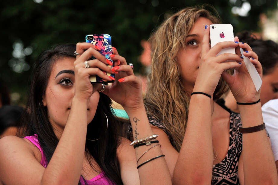 Kayla Kucewicz, left, and Elyse Tascione use their phones to record Ryan Cabrera as he performs on stage at Alive@Five at Columbus Park in Stamford on Thursday, July 11, 2013. Hearst Connecticut Newspapers are a sponsor of the event. Photo: Jason Rearick / Stamford Advocate