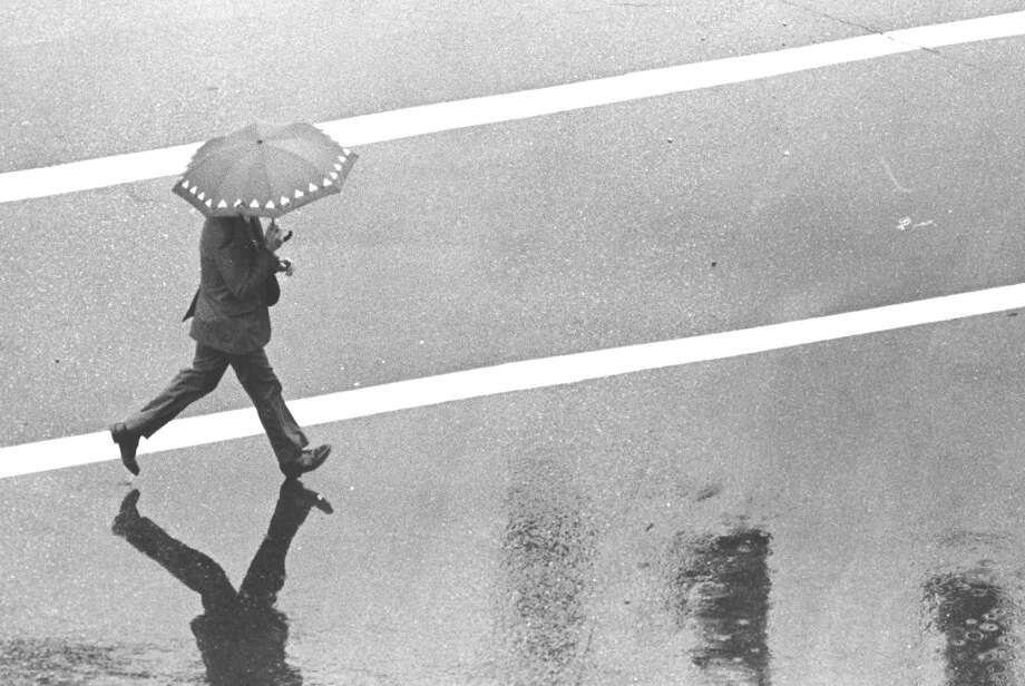 As the area endured a storm that brought 3 inches of rain over two days, a pedestrian swiftly crosses Tresser Boulevard on July 20, 1988. Photo: Advocate