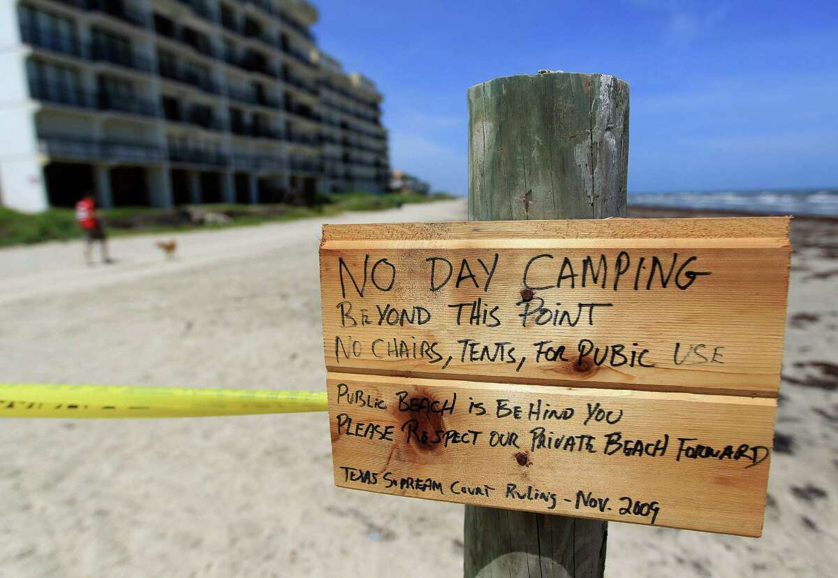 """A hand-painted sign on Hershey Beach reads """"No day camping beyond this point"""" and bans chairs or tents. """"Public beach is behind you. Please respect our private beach."""""""