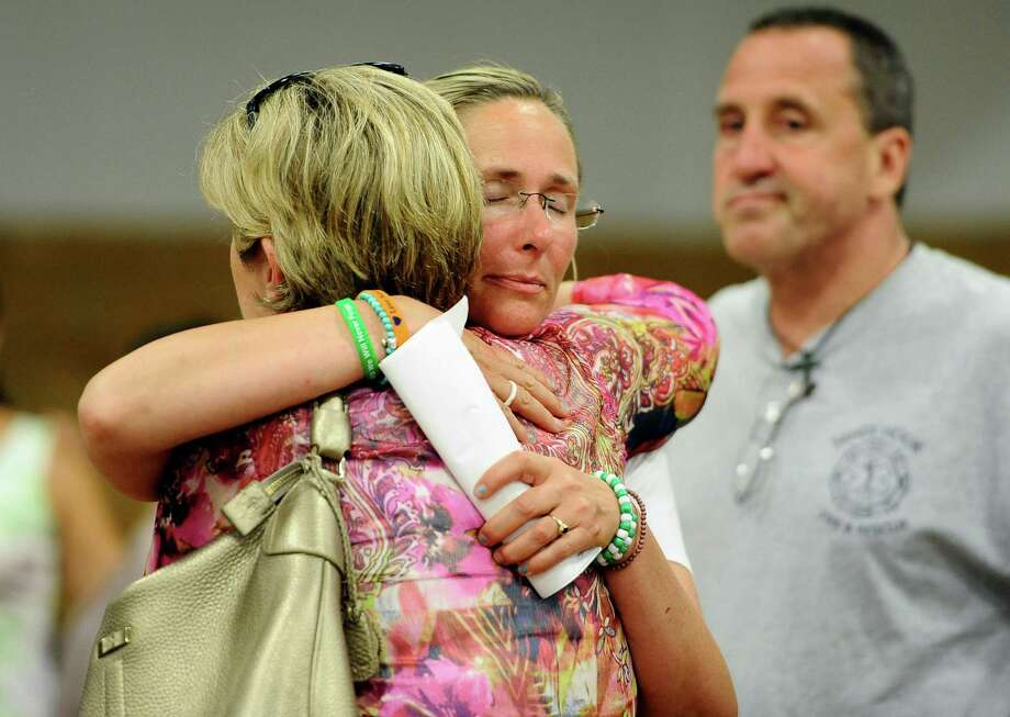Scarlett Lewis, mother of Sandy Hook Elementary School shooting victim Jesse Lewis, center, hugs Lynn McDonnell, mother, of victim Grace McDonnell, left,  as Neil Heslin, father of victim Jesse Lewis, right, looks on after a public forum on the distribution of Newtown donations at Edmond Town Hall in Newtown, Conn., Thursday, July 11, 2013.  A community foundation has been tasked with dividing up $11.4 million that was raised with the help of the United Way. At Thursday's meeting, people can comment on the disbursement of $7.7 million that has been set aside for the families of the 26 people who were killed, two wounded teachers and the families of 12 children who escaped. Photo: AP