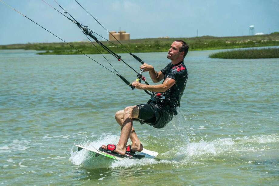 Jeff Hill of Fort Worth gets lifted onto his board while kitesurfing outside Port Aransas. Photo: Josh Trudell, For The San Antonio Express-News / Copyright 2013 Josh Trudell Photography