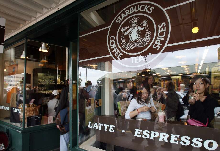 The Pike Place Market Starbucks has its business challenges. It's tiny (only 1,200 square feet), sells no food and is within a mile of three other Starbucks. But its tourist mobs and fame as the ''first'' Starbucks make it a top moneymaker. Photo: GABRIEL BOUYS, AFP/Getty Images