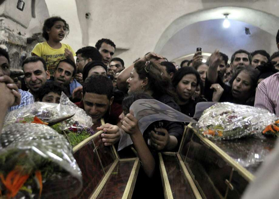 Relatives of Christians killed near Luxor pray during their funeral after violence that followed the ouster of President Mohammed Morsi. Some Christians are paying the price for their activism against Morsi and his Islamist allies. Photo: Ibrahim Zayed / Associated Press