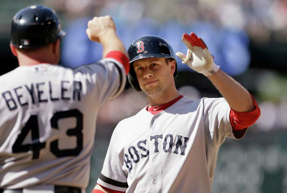 Boston Red Sox's Daniel Nava, right, is congratulated by first base coach Arnie Beyeler after hitting an RBI-single against the Seattle Mariners in the 10th inning of a baseball game on Thursday, July 11, 2013, in Seattle. The Red Sox won in 10 innings 8-7. (AP Photo/Elaine Thompson) ORG XMIT: WAET110 Photo: Elaine Thompson / AP
