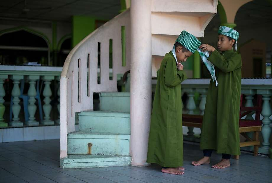 A young Muslim boy helps his friend to put on a turban at a mosque in Ampang, suburbs of Kuala Lumpur on July 11, 2013.  Islam's holy month of Ramadan is celebrated by Muslims worldwide marked by fasting, abstaining from foods, sex and smoking from dawn to dusk for soul cleansing and strengthening the spiritual bond between them and the Almighty. AFP PHOTO / MOHD RASFANMOHD RASFAN/AFP/Getty Images Photo: Mohd Rasfan, AFP/Getty Images