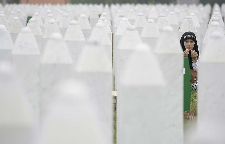 Bosnian woman Merima Nukic prays at the grave of her father during a funeral ceremony at the memorial center in Potocari, near Srebrenica, 160 kms east of Sarajevo, Bosnia, Thursday, July 11, 2013. People from around Bosnia and abroad have begun arriving in Srebrenica Thursday to commemorate 18th anniversary of the 1995 massacre and rebury recently identified victims exhumed from mass graves. The victims' bodies are still being exhumed from mass graves in the area, where Serbs had dumped them in an attempt to cover up the crime. Identified victims are buried each year on the massacre's anniversary at a memorial cemetery near Srebrenica. (AP Photo/Amel Emric) Photo: Amel Emric, Associated Press