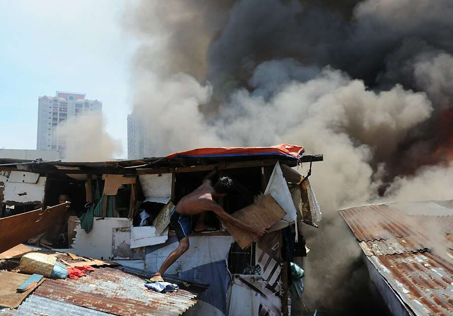 A resident destroys a wall of his house in an effort to salvage belongings as a fire engulfs a shanty town in the financial district of Manila on July 11, 2013, leaving more than 1,000 people homeless according to city officials. There were no immediate reports of casualties from the blaze, which occurred mid-morning amid government plans to relocate thousands of families living in areas vulnerable to floods and typhoons.    AFP PHOTO / TED ALJIBETED ALJIBE/AFP/Getty Images Photo: Ted Aljibe, AFP/Getty Images