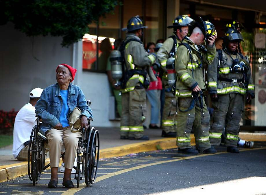Residents of the Linden Camilla Towers wait to return to their apartments after a two-alarm fire forced the evacuation of floors 1-8 in the high-rise apartment building in Memphis, Tenn. Thursday, July 11, 2013. According to Memphis Fire Department Battalion Chief Keith Staples the fire originated on with food on a stove in apartment in 710 on the seventh floor around 7:16 AM and was under control at 7:42. The department responded with 41 pieces of equipment and 97 firefighters to battle the blaze. No injuries were reported.  (AP Photo/The Commercial Appeal, Mike Brown) Photo: Mike Brown, Associated Press