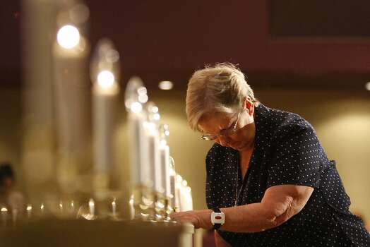 Church member Ann Bruck bows next to 35 candle lights at a vigil for 35 young victims of the crash landing of Asiana Airlines Flight 214 at San Francisco International Airport, at West Valley Christian Church on July 11, 2013 in the West Hills section of Los Angeles, California. The 35 middle- and high school-aged students were traveling from China to attend a study abroad program at West Valley Christian School. Two girls in the group, Wang Linjia and Ye Mengyuan, died at the scene of the crash. The church is collecting donations for the families of the victims. Photo: David McNew, Getty Images