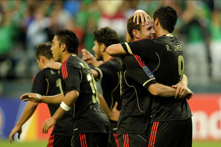 Raul Jimenez, right, is embraced by teammates following his successful shot on goal during the first half of the Mexico versus Canada CONCACAF Gold Cup soccer match Thursday, July 11, 2013, at CenturyLink Field in Seattle. Mexico led Canada 1-0 at the end of the first half and later won the game 2-0.