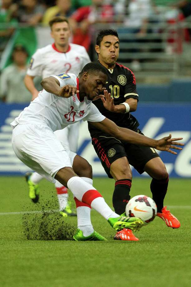 Canada's Doneil Henry, left, kicks past Mexico's Marco Fabian, right, during the first half of the Mexico versus Canada CONCACAF Gold Cup soccer match Thursday, July 11, 2013, at CenturyLink Field in Seattle. Mexico led Canada 1-0 at the end of the first half and later won the game 2-0. Photo: JORDAN STEAD, SEATTLEPI.COM / SEATTLEPI.COM