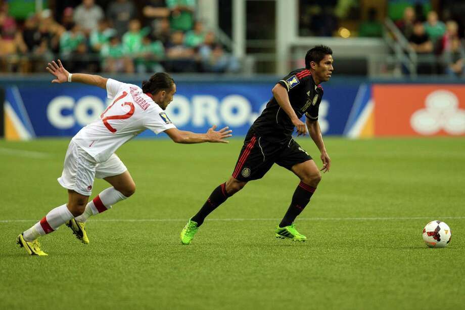 Canada's Issey Nakajima-Farran, left, pursues Mexico's Juan Carlos Valenzuela, right, during the first half of the Mexico versus Canada CONCACAF Gold Cup soccer match Thursday, July 11, 2013, at CenturyLink Field in Seattle. Mexico led Canada 1-0 at the end of the first half and later won the game 2-0. Photo: JORDAN STEAD, SEATTLEPI.COM / SEATTLEPI.COM
