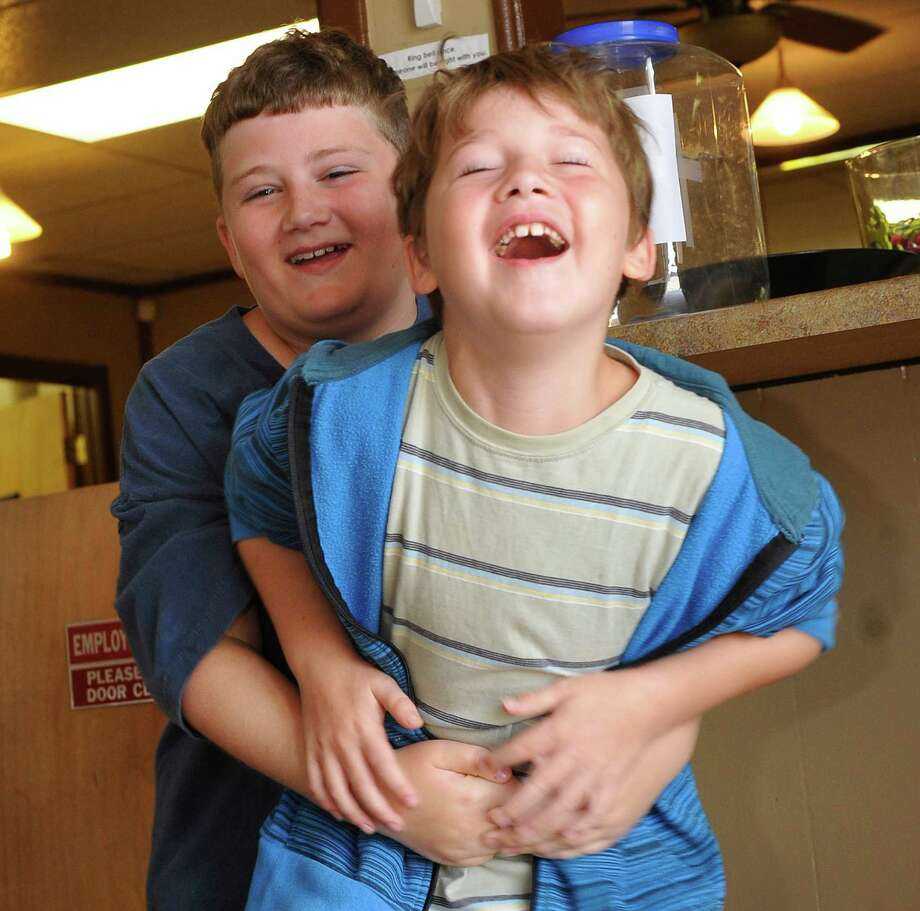 Eleven year old Jamey Lunsford, left, of Vidor, saved his nine year old brother Tanner, right,  by doing the Heimlich maneuver after he got a quarter stuck in his throat late in the evening.  Here he demonstrates how he did it based on what he remembered from watching a YouTube video. Dave Ryan/The Enterprise