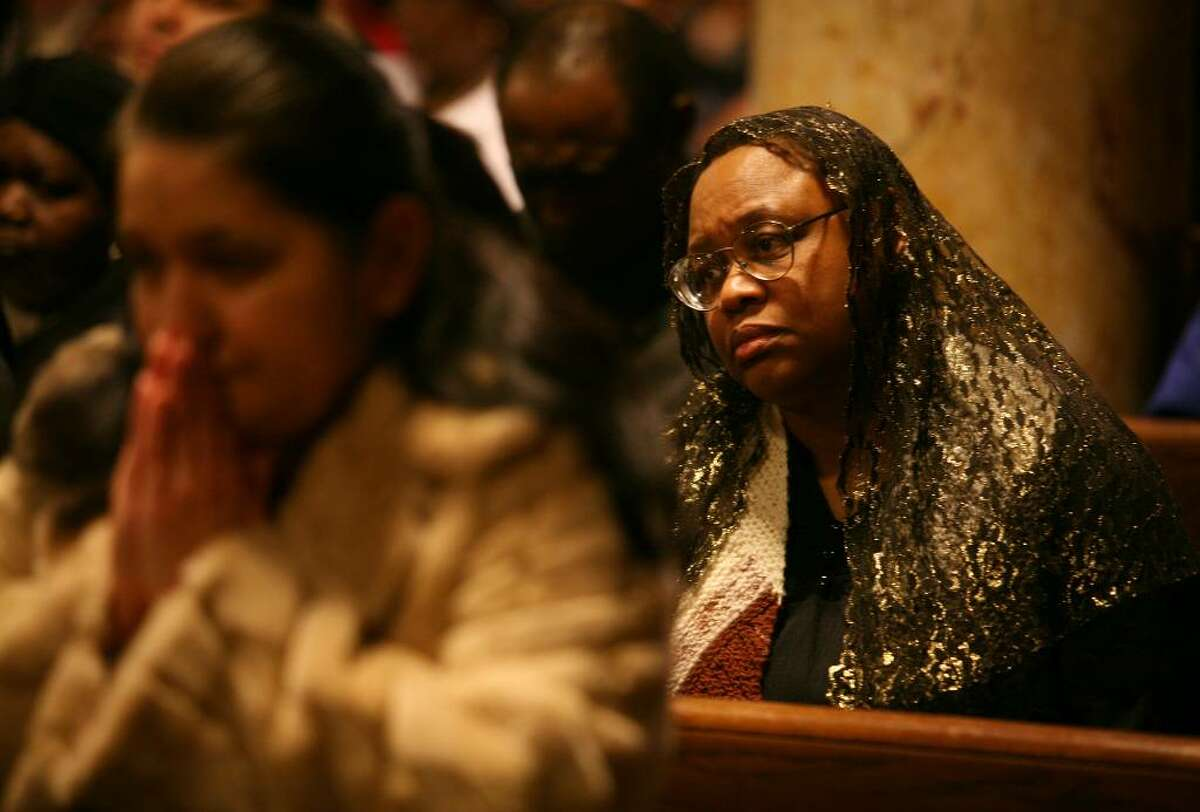 Barbara Rickman, right of Shelton, attends the memorial service for victims of the Haitian earthquake at St. Charles Borromeo Church in Bridgeport on Monday, January 18, 2010.