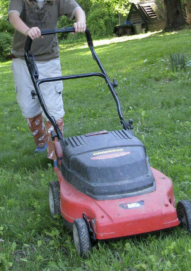 To keep grass healthy, cut it before it gets too tall. Remove no more than one-third of the height at each mowing. Photo: Associated Press