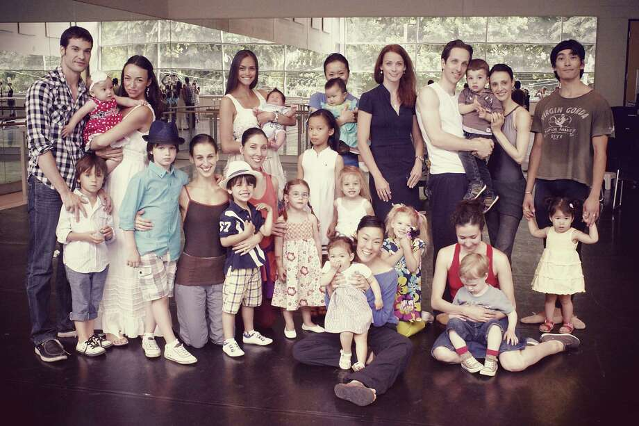 Members of the National Ballet of Canada and their children. Soloist Tanya Howard is the second woman to the left in white. She is holding her son Benjamin. Sonia Rodriguez is kneeling in front with her sons, Gabriel and Dillon. Greta Hodgkinson and husband Etienne Lavigne are at right with their son, Maxime.