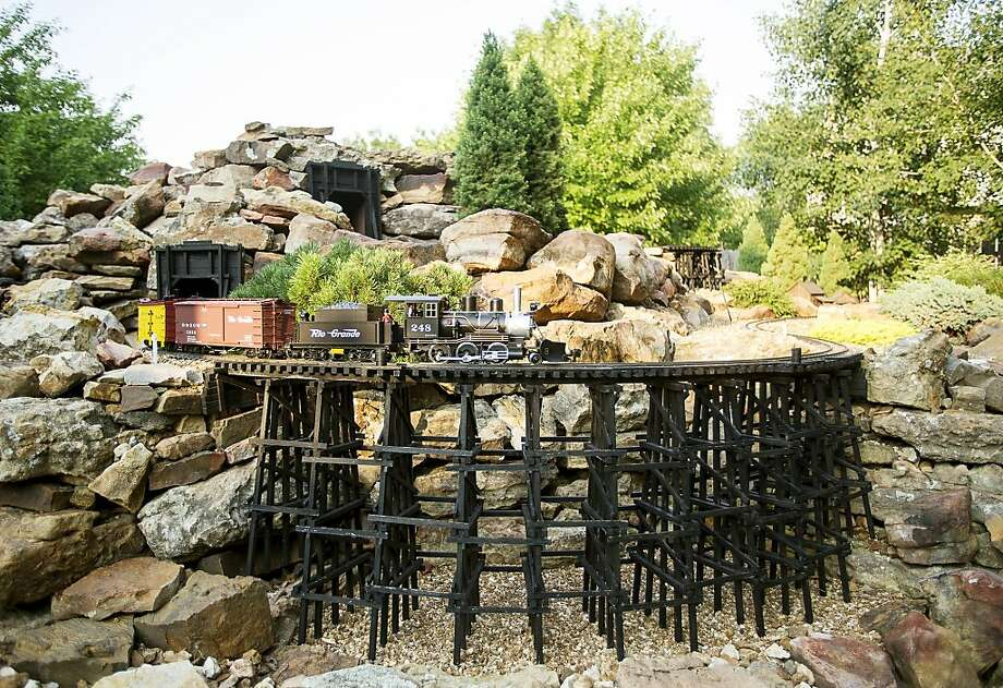 All aboard the Patio Local:Instead of planting gardenias and foxglove, train buff David   Wood turned his rock garden in Williamsburg, Neb., into a two-tiered model railroad layout,   complete with trestle. Photo: Kristin Streff, Associated Press