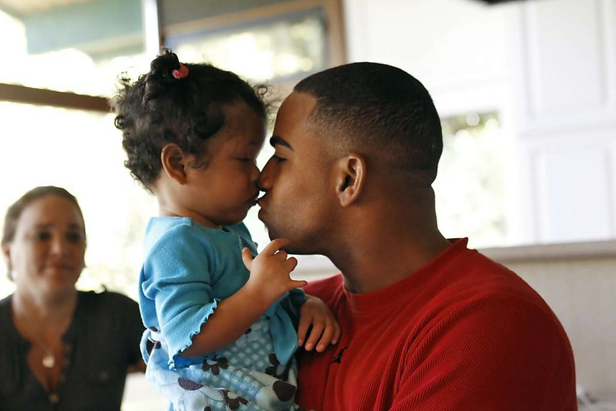 Yoenis Cespedes, of the Oakland Athletics, kisses his cousin's daughter, Yaenis Charon at his home in the Oakland hills on Friday, May 31, 2013, in Oakland, Calif. The family was finally reunited after they spent nearly a year and a half apart while Yoenis's mother and cousins struggled to travel from one carribean island to another and finally get to Florida by boat earlier this year.