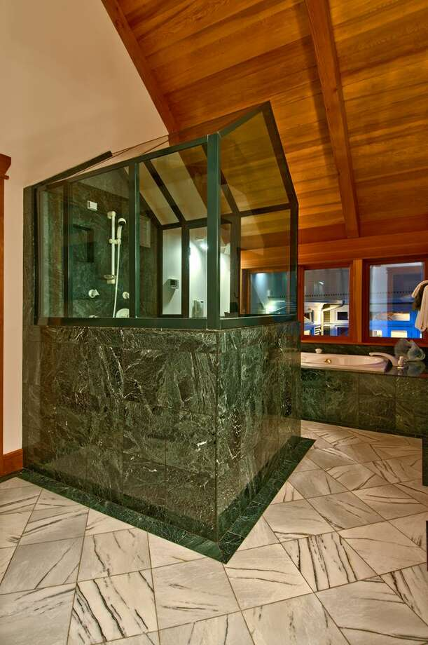 """Master bathroom of 10260 47th Ave. S.W., in Fauntleroy. The 6,530-square-foot mansion, built in 1989, has five bedrooms, 4.25 bathrooms, vaulted ceilings, a dining room that can fit more than 20 people, a parlor, a family room, an office, a """"crow's nest,"""" and multiple decks and patios on 1.75 acres. It's listed for $2.275 million. Photo: Courtesy Scott Monroe, Windermere Real Estate"""