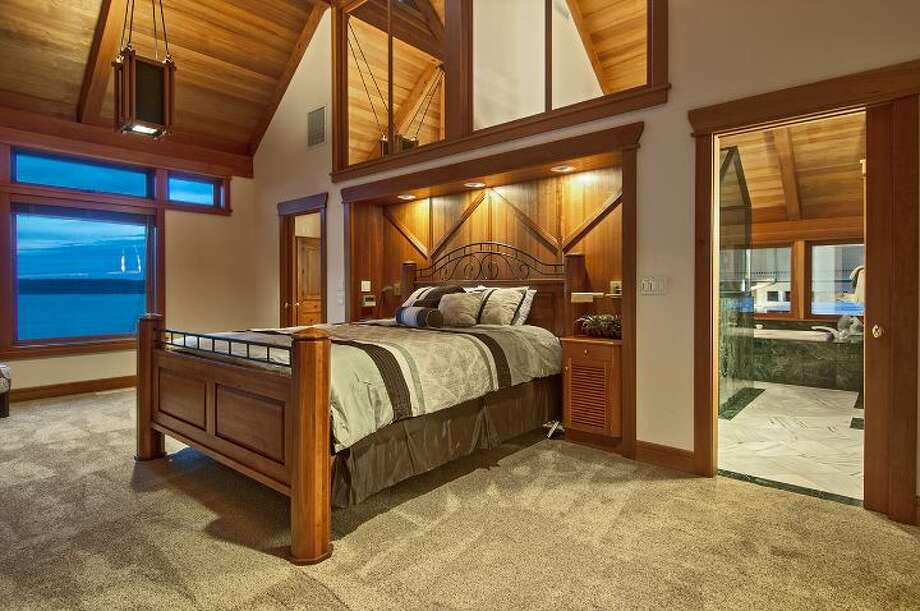 "Master bedroom of 10260 47th Ave. S.W., in Fauntleroy. The 6,530-square-foot mansion, built in 1989, has five bedrooms, 4.25 bathrooms, vaulted ceilings, a dining room that can fit more than 20 people, a parlor, a family room, an office, a ""crow's nest,"" and multiple decks and patios on 1.75 acres. It's listed for $2.275 million. Photo: Courtesy Scott Monroe, Windermere Real Estate"